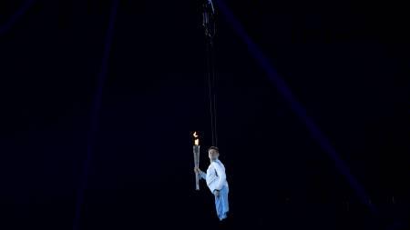 Den britiske marinesoldaten Joe Townsend bærer den paralympiske ilden mens han heises ned i Olympiastadion i London under åpningseremonien av Parcalympics onsdag kveld. (Foto: TOBY MELVILLE/Reuters)