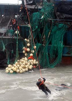 Kinesiske fiskere reddes ut av den havarerte båten sin. (Foto: Reuters)