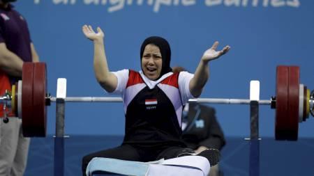 NY VERDENSREKORD: Egyptiske Fatma Omar (38) er det eldste medlemmet av Egypts paralympics-tropp. Hun lider av en medfødt tilstand som gjør at hun må bruke krykker for å holde seg oppreist. På mandag vant hun sitt andre strake gull i kvinnenes 56-kilosklasse i vektløfting. Med et løft på 141 kg slo hun også sin egen verdensrekord fra Beijing-lekene. (Foto: Lefteris Pitarakis/Ap)