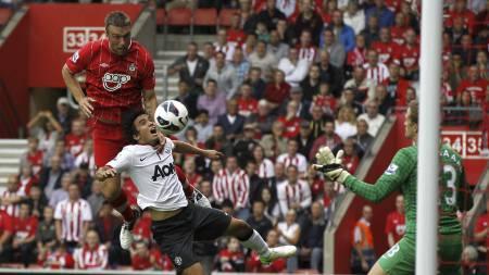 KNUSENDE OVERLEGEN: Rickie Lambert er overlegen i luftduellen med Rafael og stanger inn 1-0-ledelse for Southampton. (Foto: Sang Tan/Ap)