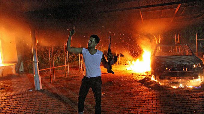 KONSULAT I BRANN: En bevæpnet mann utenfor det amerikanske konsulatet i den libyske byen Benghazi tirsdag.  (Foto: AFP)