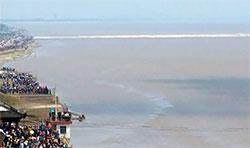 Bølgen har nådd munningen av elven. Langs kanten står folk tett i tett. (Foto: CBS)