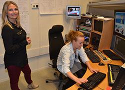 Gina Helen Pedersen styrer teknikken i værstudio, Elin kikker henne over skulderen. (Foto: Ronald Toppe)