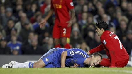 John Terry skriker av smerte etter å ha fått Luis Suárez over seg. (Foto: IAN KINGTON/Afp)