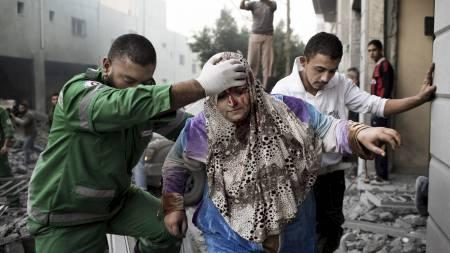 NYE ANGREP: En palestinsk kvinne fraktes ut av et bolighus som ble totalskadd under et israelsk luftangrep mot Gaza by mandag morgen. (Foto: MARCO LONGARI/Afp)