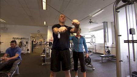 HARDTRENING: Thomas Jansen trener styrketrening med kabel under veiledning av personlig trener Anne Marte H. Sneve. (Foto: TV 2/)