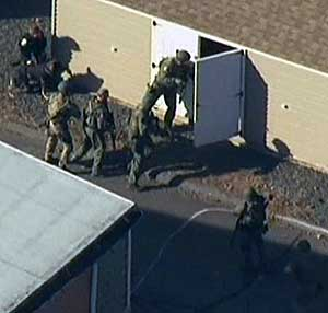 Politiet søker gjennom en bygning inne på skolens område.
