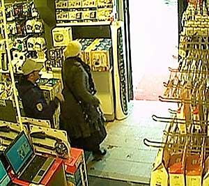 Her ser vi en utenlandsk kvinne som fikk hjelp til å stappe to datamaskiner innenfor skjørtet, før paret spaserte ut av butikken.