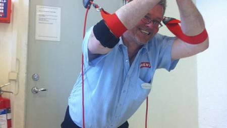 SLYNGERENING: Hans har brukt slynger for å rette opp i ubalanser i muskulaturen. Her gjør han noen øvelser på jobb på Meny Oppsal. (Foto: Privat/)