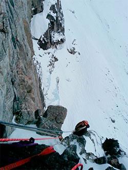 Andrew Kirkpatrick sitter på en hylle. Det er så bratt i den delen av Trollveggen de tre klatrer at det samler seg lite snø. (Foto: Privat)