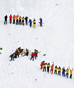 Sveitsiske redningsmannskaper bruker søkestenger for å finne tre mennesker som ble tatt av skred i Diemtig-dalen i januar 2010. Alle tre ble gravd frem døde. (Foto: Ap)
