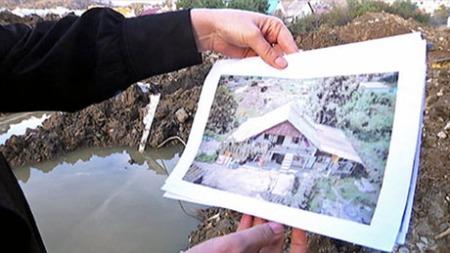 JEVNET MED JORDEN: Tatiana står på sin gamle tomt og viser bilder av huset. Slik så det ut før bulldoserne kom. (Foto: TV 2)