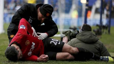 SJEKKET: Uniteds støtteapparat sjekker Robin van Persie etter hendelsen. (Foto: STEFAN WERMUTH/Reuters)