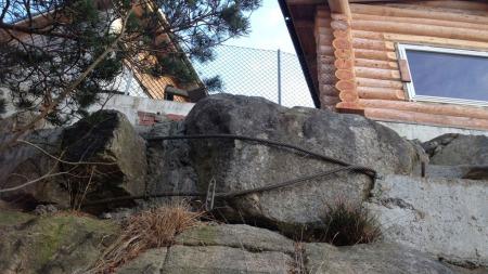 SIKRING: Brødrene Jørmeland, som bygde den ulovlige muren, har forsøkt å sikre en stor stein med en løs vaier. Ikke bra nok, sier fagfolk. (Foto: TV 2 Hjelper deg )