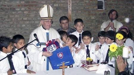 DA HAN VAR KARDINAL: Jorge Mario Bergoglio holder opp en klubbvimpel i et møte med skolebarn i Buenos Aires. (Foto: STR/Afp)