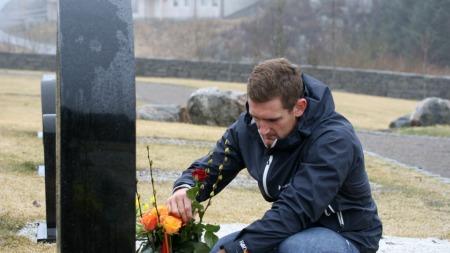 EN BLOMST TIL MINNE: Cameron van der Burgh plasserer en rose ved Alexander Dale Oens grav (Foto: Sander Smørdal, ©TV 2)