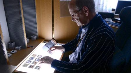 LYSBILDER: Kjell Lutnes går igjennom de gamle lysbildene. (Foto:   TV 2)