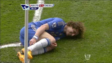 David Luiz ligge rnede og virker å smile etter at han ble sparket ned av Rafael, som ble utvist. (Foto: TV 2)