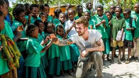 Stian Blipp får high five i Zambia (Foto: Plan Norge)