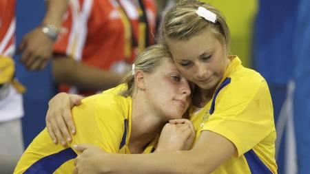 Sveriges Johanna Alm (t.v.) og Isabelle Gulldén klemmer hverandre etter tap for Norge i OL i Beijing i 2008. (Foto: Lee Jin-man/AP)
