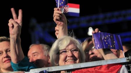 FEIRING: En kvinne holder opp fredstegnet og feirer at Kroatia endelig er innlemmet i Europaunionen. (Foto: Reuters)