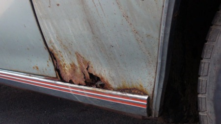 Forskjermene ser ut til å være de delene av bilen som er hardest   angrepet av rust. Men pyntelistene både i skjermkantene og langs kanalene   er på plass. (Foto: eBay.com)