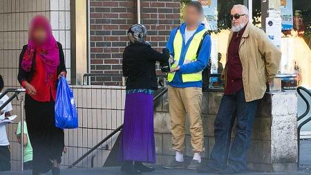 Faren til et tidligere Profetens Ummah-medlem fra Algerie står   sammen med en av bøssebærerne ved T-banestasjonen på Grønland i Oslo.