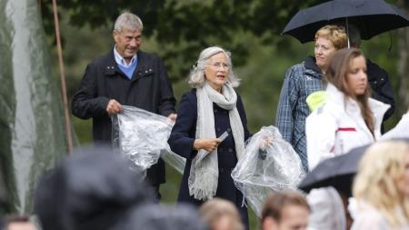 VÅTT: Gjestene fikk utdelt regnponcho da de ankom Dronningparken. Her takker jubilantens mor, Marit Tjessem (75) og hennes kjæreste  Magnar Alfred Fjeldvær (76) ja til.  (Foto: Scanpix)