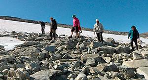 Arkeologene går manngard i et område der snøfonnen er smeltet bort. (Foto: Harald Jacobsen / TV 2)
