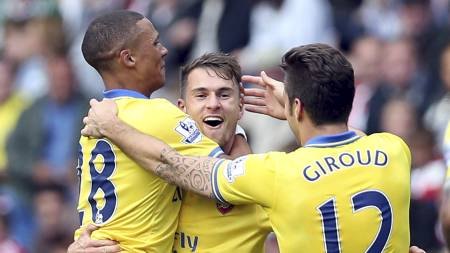 FORTJENT HYLLEST: Aaron Ramsey gratuleres av Kieran Gibbs og Olivier Giroud etter scoring for Arsenal. (Foto: Ian MacNicol/Afp)