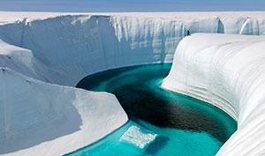 En elv av smeltevann renner oppå isen som dekker Grønland. (Foto: James Balog / Ap Photo)