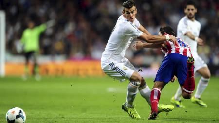 TØFFE TAK: Gareth Bale i duell med Diego Godín i sin første kamp på Santiago Bernabéu. (Foto: EMPICS/Pa Photos)