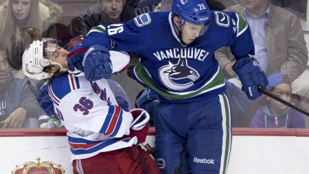 Vancouver   Canucks defenceman Frank Corrado (26) puts New York Rangers right wing   Mats Zuccarello (36), of Norway, into the boards during the third period   of NHL pre-season hockey action in Vancouver, British Columbia. (AP Photo/The   Canadian Press, Jonathan Hayward) (Foto: Jonathan Hayward/Ap)