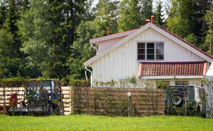 Noen meter unna en traktor og jordbruksredskaper står en bil   fra Forsvaret parkert. Fargen er ikke lik den vanlige olivengrønne.