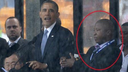 HVEM ER HAN?: Mannen på Obamas venstre side er i hvert fall ingen døvetolk.  (Foto: AFP PHOTO / ALEXANDER JOE)