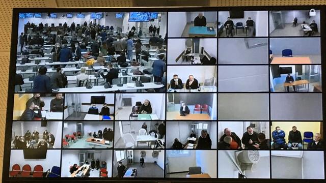 Schermo che mostra diversi imputati tra gli oltre 300 imputati durante la giornata di apertura del processo).