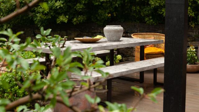 Zona pranzo: tavoli e sedie con superfici in cemento.