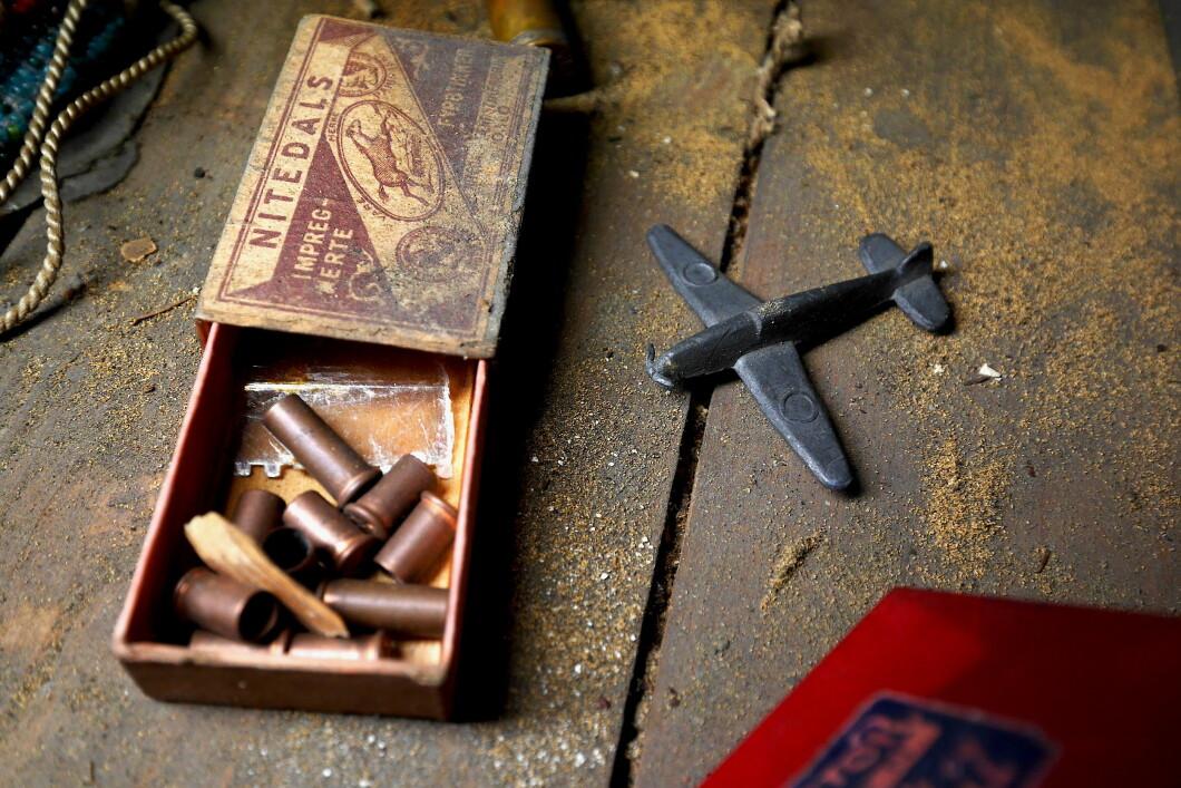 Una vecchia scatola di fiammiferi con bossoli usati e un modello in metallo di un combattente Messerschmidt tedesco.