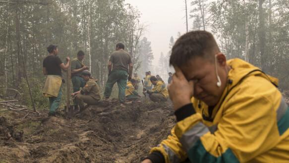 I dipendenti del servizio forestale russo scavano una trincea per fermare un incendio a ovest di Yakostik.