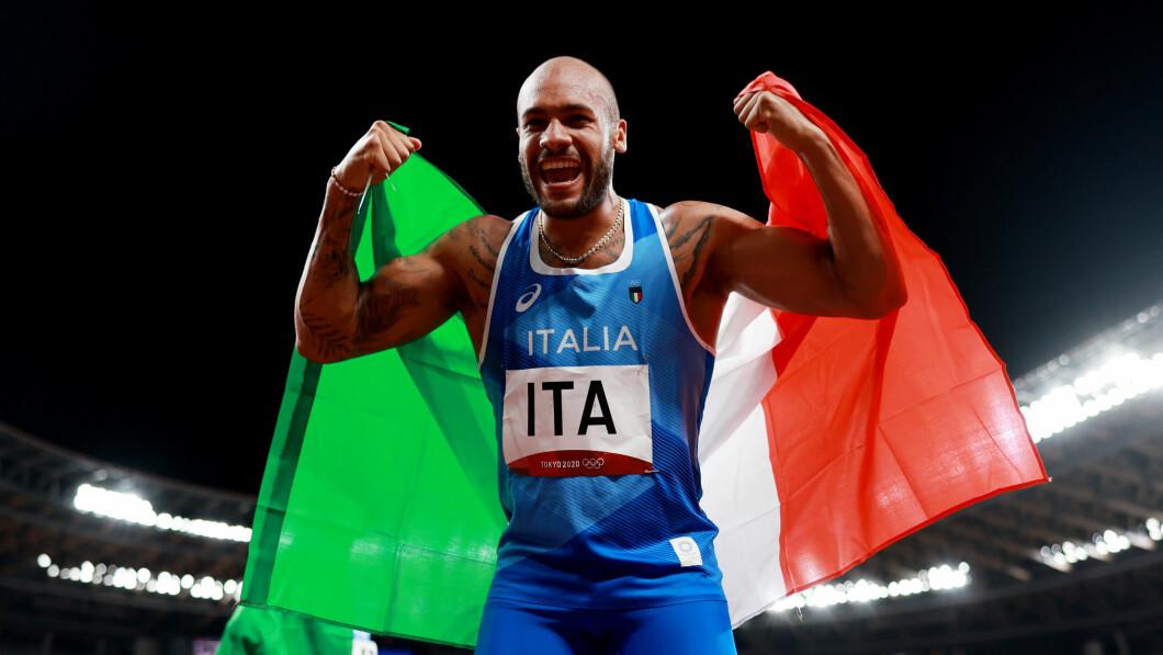 Marcel Jacobs esulta con la bandiera italiana per la staffetta d'oro.