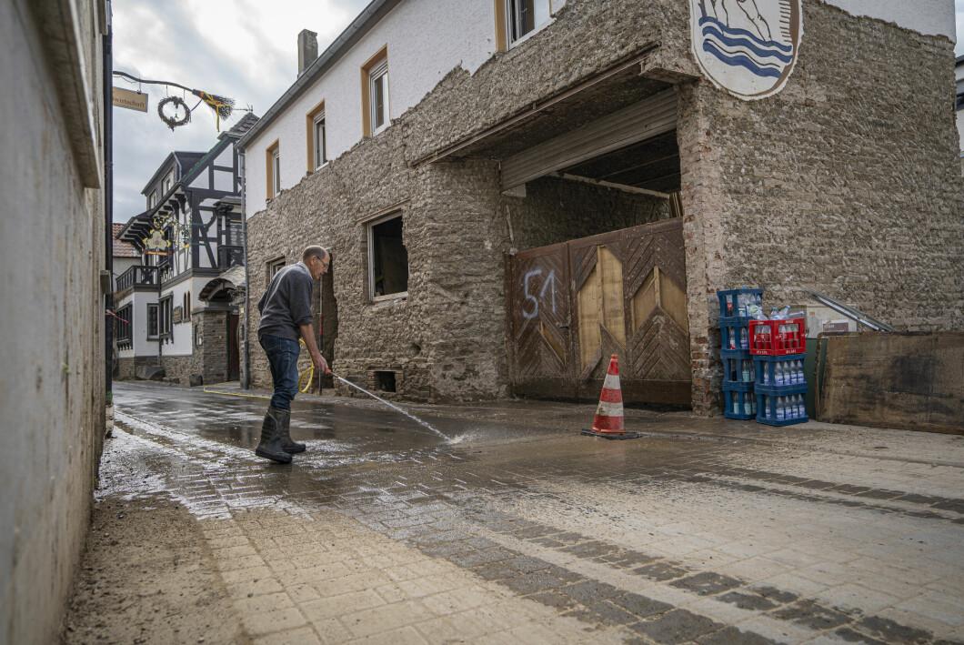 Un uomo lava le strade del villaggio di Dinau.