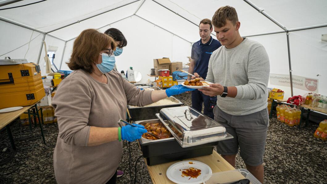 I volontari distribuiscono cibo alle vittime delle inondazioni e ai soccorritori a Rish.